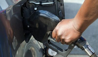 Dane Ellis, a full-service attendant at the Exxon station at Fourth Street and Pennsylvania Avenue Southeast in Washington, fills a car with gas on Monday, April 11, 2011. (The Washington Times)