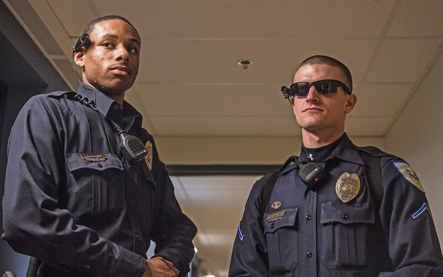 Officer Carl Johnson and Officer Matthew Jordan, of the Laurel Police Department, wear Taser Axon Flex cameras. The department is testing the cameras before deploying them in the field. The cameras are meant to protect police officers from complaints. (Andrew S. Geraci/The Washington Times)