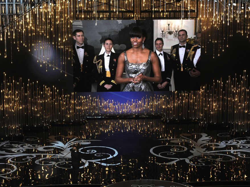 First lady Michelle Obama, appearing on-screen from Washington, and actor Jack Nicholson present the award for best picture during the Oscars at the Dolby Theatre in Los Angeles on Sunday, Feb. 24, 2013. (Chris Pizzello/Invision/Associated Press)