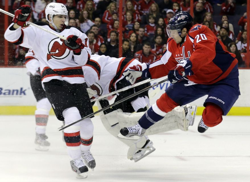 Washington Capitals right wing Troy Brouwer (20) goes airborne after colliding with New Jersey Devils goalie Johan Hedberg (1), from Sweden, with right wing Steve Bernier (18) nearby, in the third period of an NHL hockey game Saturday, Feb. 23, 2013 in Washington. The Capitals won 5-1. (AP Photo/Alex Brandon)