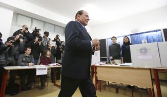 Former Italian Premier Silvio Berlusconi casts his ballot in Milan on Sunday, Feb. 24, 2013. Italy voted in a watershed parliamentary election Sunday and Monday that could shape the future of one of Europe's biggest economies. (AP Photo/Antonio Calanni)
