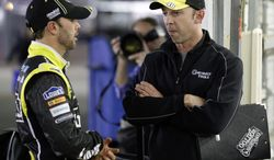 Jimmie Johnson, left, talks with his crew chief, Chad Knaus, outside his garage after practice for the NASCAR Sprint Unlimited Shootout auto race at Daytona International Speedway, Friday, Feb. 15, 2013, in Daytona Beach, Fla. (AP Photo/John Raoux)