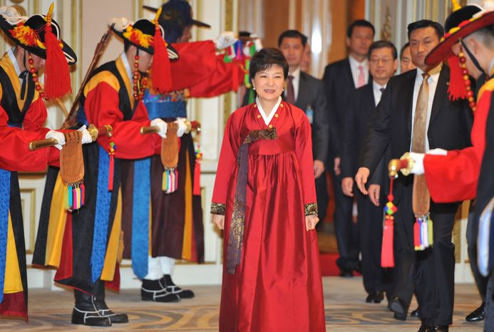 ** FILE ** Park Geun-hye (center), South Korea's new president, arrives for the official dinner at the presidential Blue House in Seoul on Monday, Feb. 25, 2013. Ms. Park took off