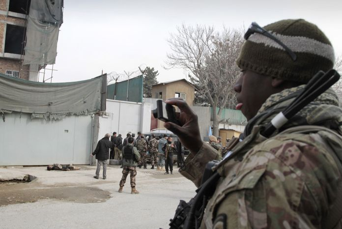 A U.S. soldier (right) photographs the scene where an insurgent was shot to death near an Afghan intelligence office in Kabul, Afghanistan, on Sunday, Feb. 24, 2013. A series of early morning attacks hit in the nation's east on Sunday, with three separate suicide bombings in outlying provinces and a shootout between security forces and a would-be attacker in the capital. (AP Photo/Musadeq Sadeq)