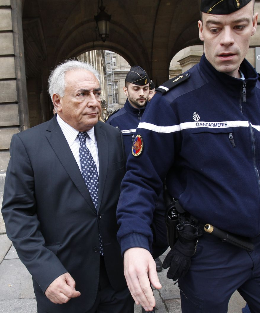 Dominique Strauss-Kahn (left), former International Monetary Fund chief, leaves a Paris courthouse on Tuesday, Feb. 26, 2013, after filing a lawsuit over a new book about a past relationship. (AP Photo/Christophe Ena)