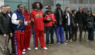 "Flamboyant former NBA star Dennis Rodman (fifth from right) poses with three members of the Harlem Globetrotters basketball team (in red jerseys) and a media production crew upon their arrival at the Pyongyang airport in North Korea on Tuesday, Feb. 26, 2013. Rodman, known as ""The Worm,"" is an unlikely ambassador for sports diplomacy at a time of heightened tensions between the U.S. and North Korea. (AP Photo/Kim Kwang Hyon)"