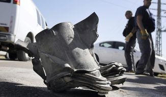 Israeli explosives experts stand by an rocket fired from the northern Gaza Strip that landed near the coastal city of Ashkelon, Tuesday, Feb. 26, 2013. It was the first such projectile from the Palestinian territory to hit Israel since Israel-Gaza hostilities last November. (AP Photo/Tsafrir Abayov)