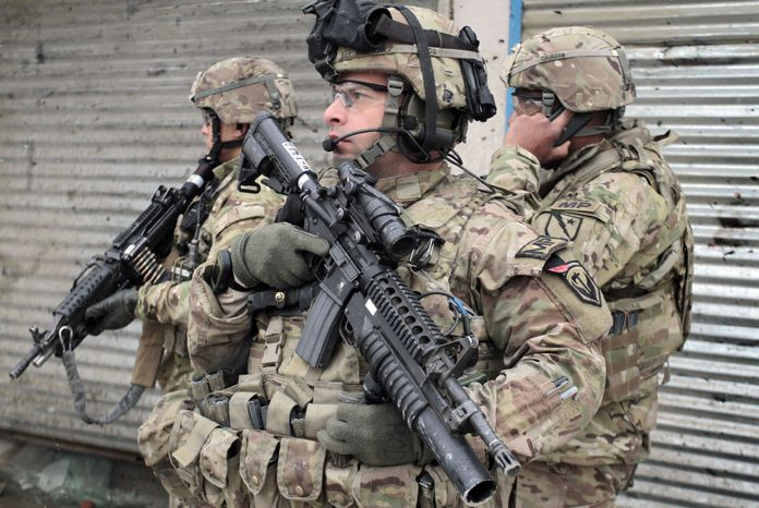 ** FILE ** U.S. soldiers stand guard at the scene of a suicide attack in Kabul, Afghanistan, Wednesday, Fe