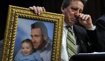 Neil Heslin, the father of a six-year-old boy who was slain in the Sandy Hook massacre in Newtown, Conn., on Dec. 14, holds a picture of himself with his son and wipes his eye while testifying on Capitol Hill on Feb. 27, 2013, before the Senate Judiciary Committee on the Assault Weapons Ban of 2013. (Associated Press)