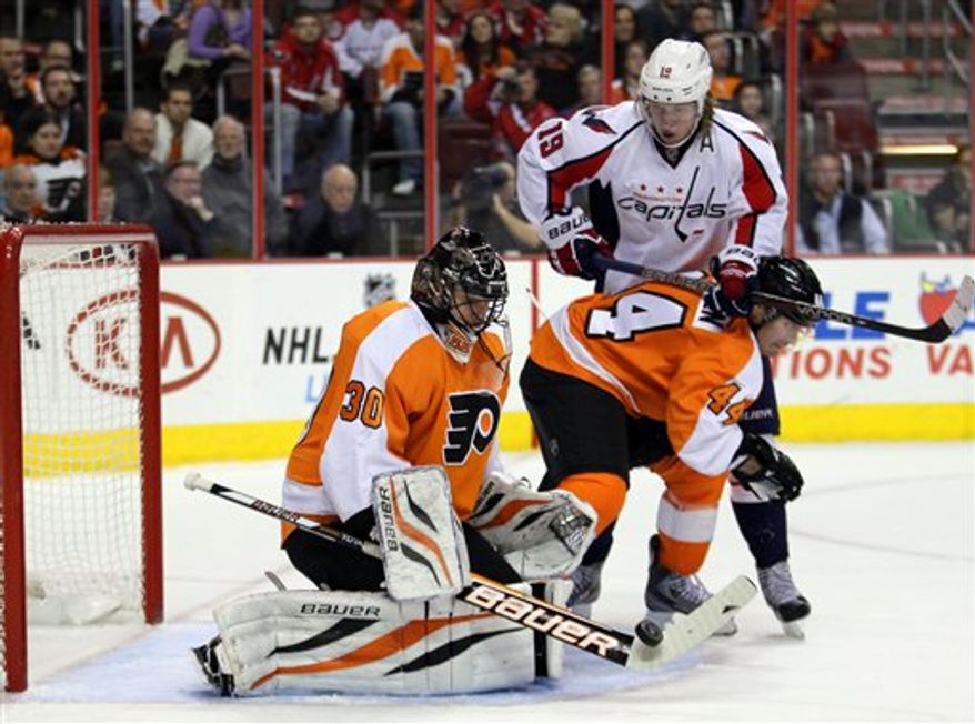 Philadelphia Flyers goalie Ilya Bryzgalov, left, deflects the pucks as teammate Kimmo Timonen (44) blocks the path of Washington Capitals Niklas Backstrom in the first period of an NHL hockey game on Wednesday, Feb 27, 2013, in Philadelphia. (AP Photo/Tom Mihalek)