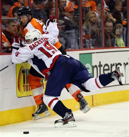 Philadelphia Flyers' Bruno Gervais (27) is pinned to the boards by Washington Capitals' Nicklas Backstron (19) in the third period of an NHL hockey game on Wednesday, Feb 27, 2013, in Philadelphia. The Flyers won 4-1. (AP Photo/Tom Mihalek)
