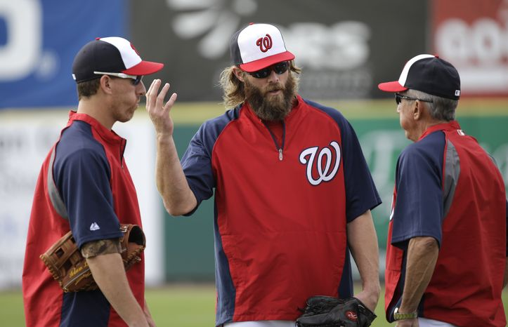 Washington Nationals outfielder Jayson Werth, center, and first baseman Adam LaRoche, left, talk with manager Davey Johnson, right, before an exhibition spring training baseball game against the Miami Marlins Wednesday, Feb. 27, 2013, in Viera, Fla. (AP Photo/David J. P