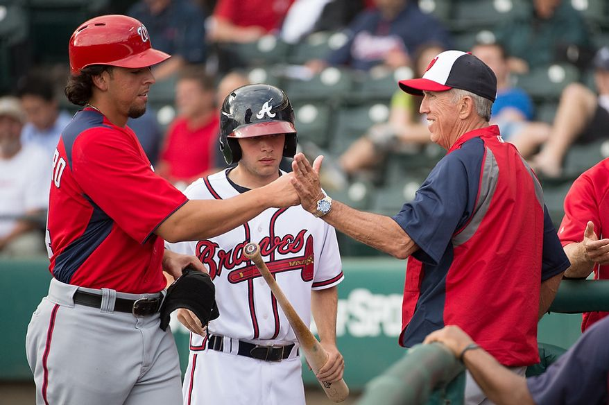 Washington Nationals first baseman Chris Marrero (14), left, gets congratulated by Washington Nationals manager Davey Johnson (5), right, after scoring as the Washington Nationals play the Atlanta Braves during spring training at Champion Stadium, Kissimmee, Fla., Tuesday, February 26, 2013. (Andrew Harnik/The Washington Times)