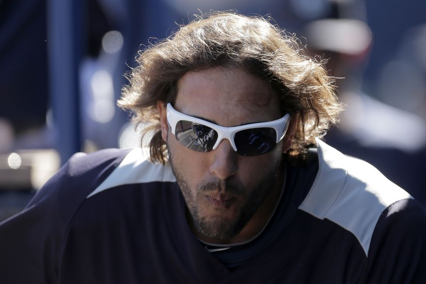Seattle Mariners left fielder Michael Morse watches from the dugout during an exhibition baseball game against the San Diego Padres Friday, Feb. 22, 2013, in Peoria, Ariz. (AP Photo/Charlie Riedel)