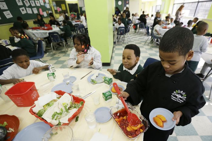 ** FILE ** A student serves up dessert to classmates during lunch at the People for People Charter School on Monday, Feb. 25, 2013, in Philadelphia