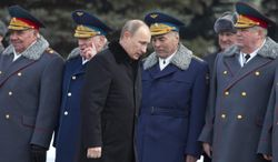 Russian President Vladimir Putin, center, attends a wreath-laying ceremony at the Tomb of the Unknown Soldier in Moscow, Russia, Saturday, Feb. 23, 2013. The Defenders of the Fatherland Day, celebrated in Russia on Feb. 23, honors the nation's military and is a nationwide holiday. (AP Photo/Misha Japaridze)