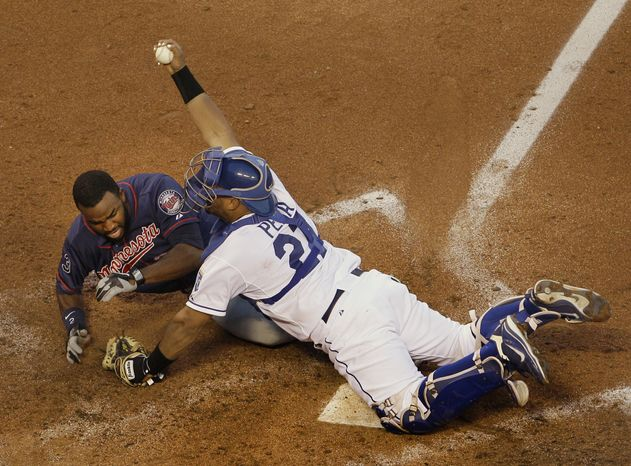 Minnesota Twins' Denard Span, left, is forced out at home by Kansas City Royals catcher Brayan Pena (27) while trying to stretch a triple during the fourth inning of a baseball game on Friday, June 3, 2011, in Kansas City, Mo. (AP Photo/Charlie Riedel)