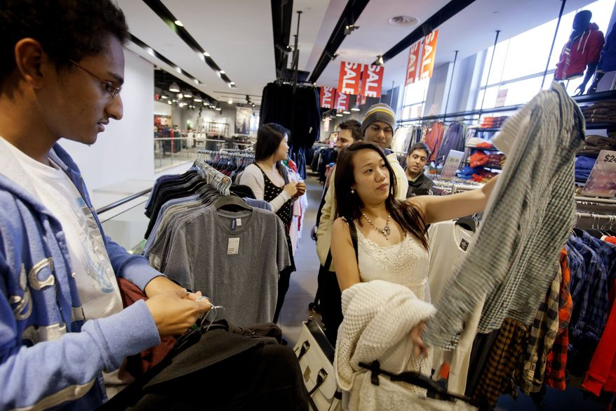 ** FILE ** In this Wednesday, Dec. 12, 2012, photo, Lana Nguyen, right, holds up a shirt while helping friend Chris Ghiathi, left, shop in an H&M store, in Atlanta. (AP Photo/David Goldman)