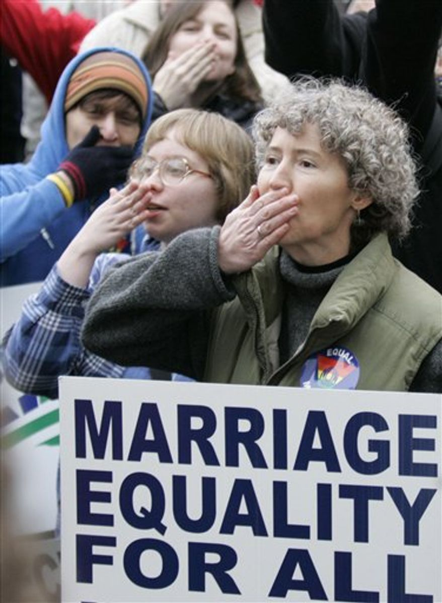 ** File ** Natalie Warrens, right, of Portland, Ore., is seen with others as they blow a kiss in the direction the of the Oregon Supreme Court during a rally at the Capitol in Salem, Ore. in support of same-sex marriage, 2004. (AP Photo/Rick Bowmer, file)