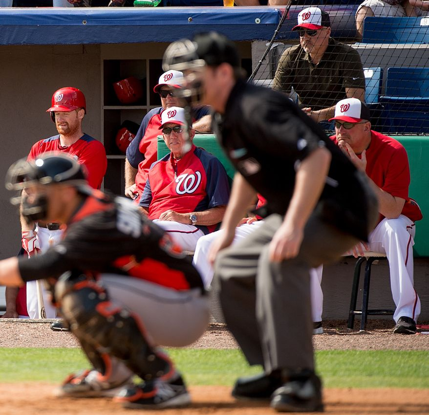 Washington Nationals manager Davey Johnson (5), center, and Washington Nationals general manager Mike Rizzo, top right, watch as the Washington Nationals play the Florida Marlins during spring training at Space Coast Stadium, Viera, Fla., Wednesday, February 27, 2013. (Andrew Harnik/The Washington Times)