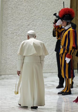 Pope Benedict XVI walks past a Swiss guard as he leaves at the end of his weekly general audience in the Paul VI Hall at the Vatican, Wednesday Feb. 13, 2013. The 85-year-old Benedict basked in more than a minute-long standing ovation when he entered the packed audience hall for his traditional Wednesday general audience. He was interrupted by applause by the thousands of people, many of whom had tears in their eyes. (Associated Press)