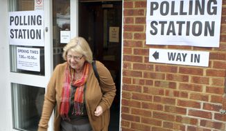 A resident leaves the polling station after casting her vote in the Eastleigh by-election in West End, Hampshire, southern England Thursday, Feb. 28, 2013. Britain's political parties are contesting a special election after a campaign overshadowed by scandals, including the criminal conviction of a former Cabinet minister and allegations of sexual misconduct against a party official. (AP Photo/Steve Parsons/PA)