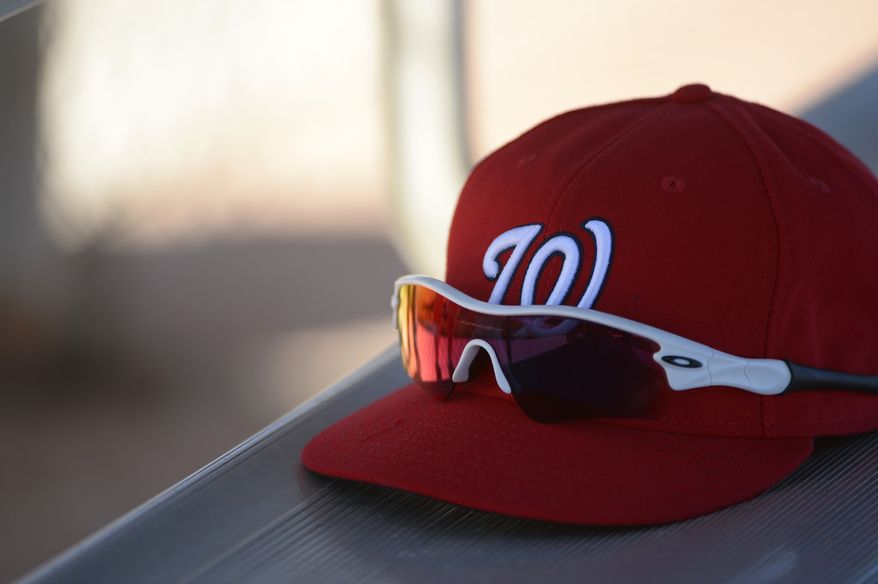 A Washington Nationals player's hat and sunglasses sit in the dugout during spring training baseball in Viera, Fla., Wednesday, Feb. 20, 2013.(AP Photo/Phelan M. Ebenhack)