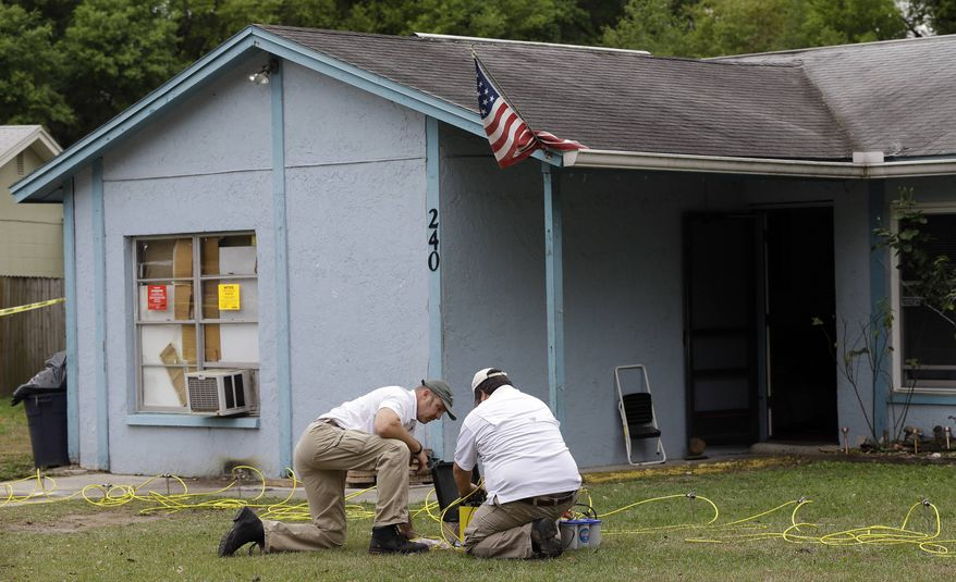 Engineers work in front of a home where sinkhole opened up underneath a bedroom and swallowed a man Friday, March 1, 2013, in Seffner, Fla. (AP Photo/Chris O'Meara)