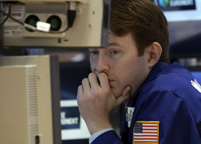 Specialist Peter Elkins works on the floor of the New York Stock Exchange on March 1, 2013. (Associated Press)