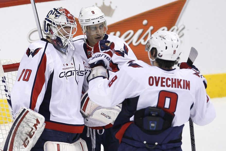 Washington Capitals' Tomas Mike Ribeiro (9) and Alex Ovechkin (8) celebrate goaltender Braden Holtby's (70) shutout against the Winnipeg Jets during third-period NHL hockey game action in Winnipeg, Manitoba, Saturday, March 2, 2013. (AP Photo/The Canadian Press, John Woods)