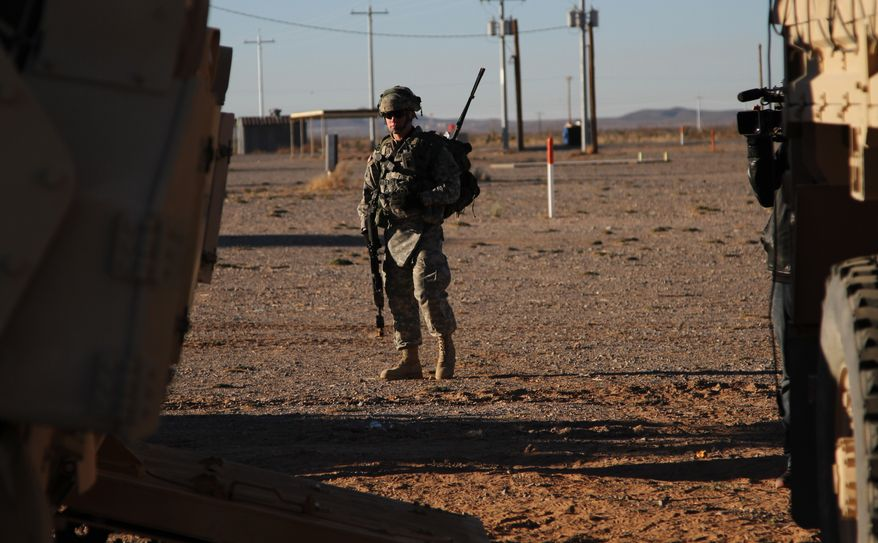 A soldier stands near a tank and a truck before a training exercise in Fort Bliss, Texas, on Wednesday, Jan. 23, 2013. The Army is rolling out a new training platform that allows the integration of live units, simulators and computer-generated forces. It is expected to allow cheaper, more frequent training. (AP Photo/Juan Carlos Llorca)