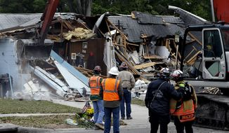 Demolition experts watch as the home of Jeff Bush, 37, is torn down on Sunday, March 3, 2013, after a sinkhole opened up underneath it late Thursday evening and swallowed Mr. Bush, 37, in Seffner, Fla. The house almost covered the 20-foot-wide opening of the sinkhole, and rescuers said there were no signs of life. (AP Photo/Chris O'Meara)