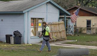 ** FILE ** On Saturday, March 2, 2013, an engineer tethered with a safety line walks in front of a house where a sinkhole opened up underneath a bedroom late Thursday evening and swallowed a man in Seffner, Fla. (AP Photo/Chris O'Meara)