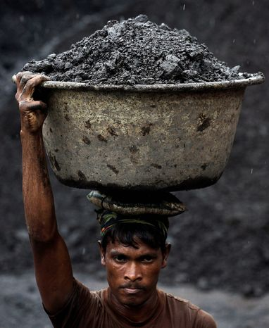 Coal is a cheaper fuel source in the developing world, including India, where a worker carries coal to load onto a truck at a depot in Gauhati. India and other countries are building coal power plants to meet demand as its economy grows. (Associated Press)