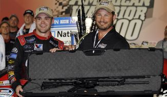 **FILE** Ricky Stenhouse Jr., left, poses with the rifle he won with retired U.S. Special Forces soldier Greg Stube in victory lane after winning the NASCAR Nationwide Series auto race at Atlanta Motor Speedway, Saturday, Sept. 1, 2012, in Hampton, Ga. (AP Photo/Rainier Ehrhardt)