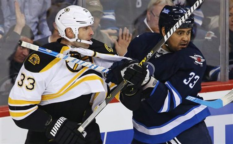 Boston Bruins' Zdeno Chara (33) battles with Winnipeg Jets' Dustin Byfuglien (33) during the first period of their NHL hockey game, Sunday, Feb. 17, 2013, in Winnipeg, Manitoba. (AP Photo/The Canadian Press, Trevor Hagan)