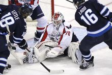 Washington Capitals goaltender Braden Holtby (70) saves a shot from Winnipeg Jets' Andrew Ladd (16) as Bryan Little (18) looks for the rebound during third-period NHL hockey game action in Winnipeg, Manitoba, Saturday, March 2, 2013. (AP Photo/The Canadian Press, John Woods)