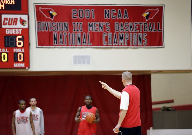 In this photo taken Feb. 12, 2013, Catholic University coach Steve Howes talks to his team during NCAA college basketball practice in Washington. Heard about the Catholic 7, those like-minded schools planning to break away from Big East? Right now, they've got nothing on the Catholic 2, the men's and women's teams at the Division III Catholic University who are a combined 42-4. (AP Photo/Alex Brandon)