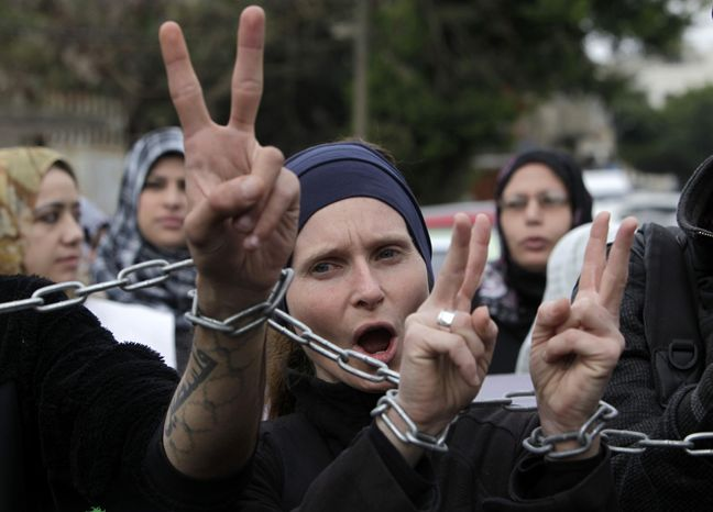 ** FILE ** Palestinians and foreign activists chant slogans as they march with their hands chained together during a protest held in solidarity with Palestinian prisoners held in Israeli j