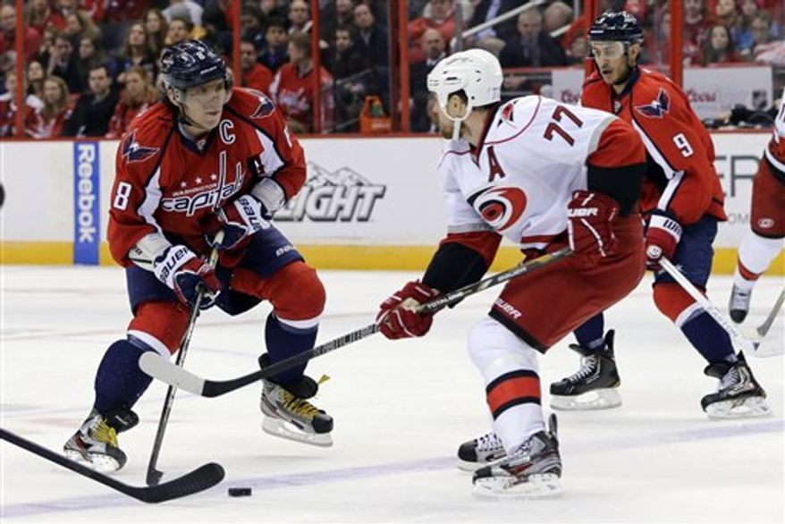 Washington Capitals left wing Alex Ovechkin (8), from Russia, tries to control the puck as Carolina Hurricanes defenseman Joe Corvo (77) skates in, during the first period of an NHL hockey game Tuesday, Feb. 26, 2013, in Washington. (AP Photo/Alex Brandon)