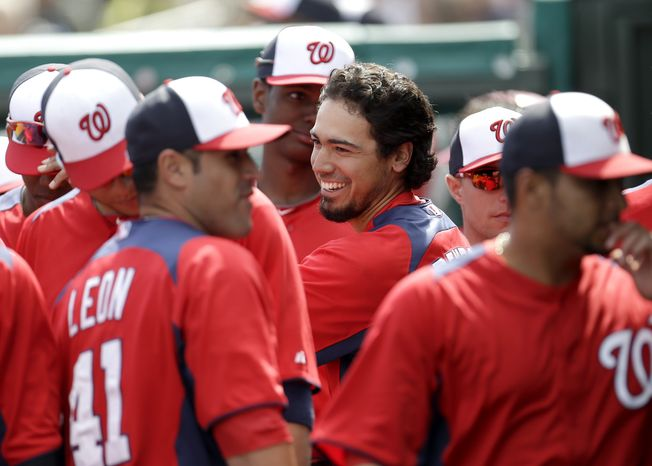 Washington Nationals' Anthony Rendon, center, is congratulated in the dugout after hitting a home run off St. Louis Cardinals starting pitcher Adam Wainwright during the second inning of an exhibition spring training baseball game, Saturday, March 2, 2013, in Jupiter, Fla. (AP Photo/Julio Cortez)