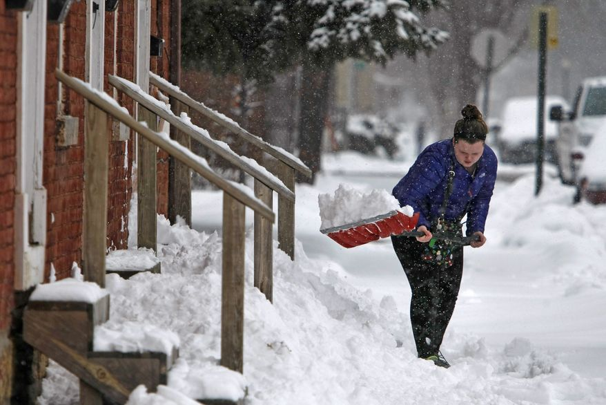 Nikki Nutter scoops heaps of snow from the front of her Dubuque, Iowa, home Wednesday, Feb. 27, 2013. The Dubuque area was hit last night with a winter storm dumping snow across the tristate area. (AP Photo/The Telegraph Herald, Jeremy Portje)
