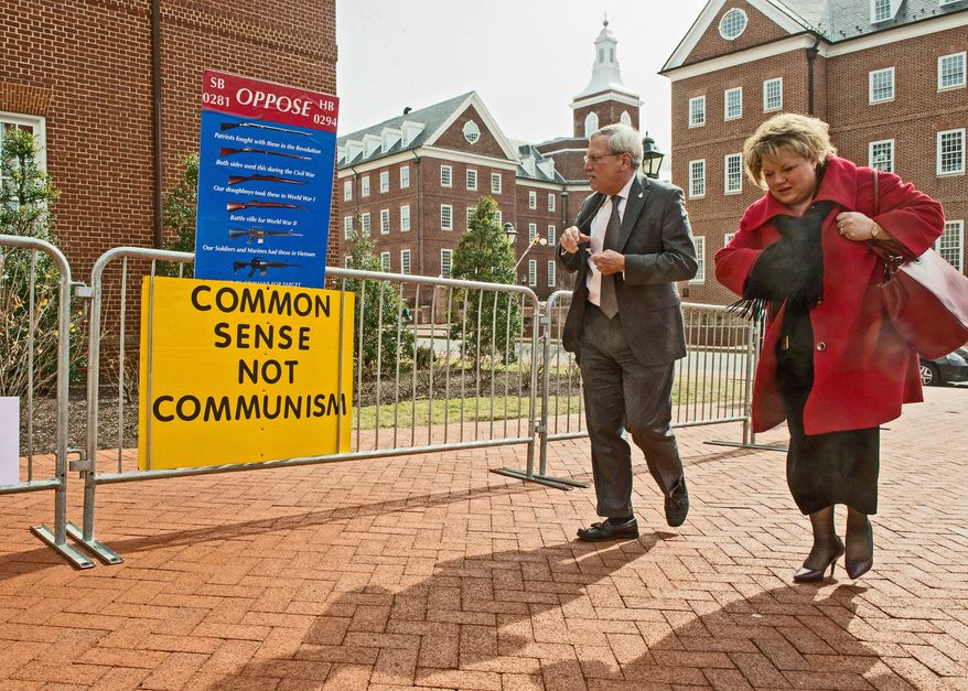 photographs by andrew harnik/the washington times Posters opposing gun control bills before the Maryland General Assembly line a walkway outside the Lowe House Office Building in Annapolis  where hundreds waited to speak their mind Tuesday. Among them was Tim Rourke of Mechanicsville, Md. (below), who says he waited until 3 a.m. to testify Friday, watches a video feed of the House Judiciary Committee with others while waiting to give testimony on their opposition to the bills.