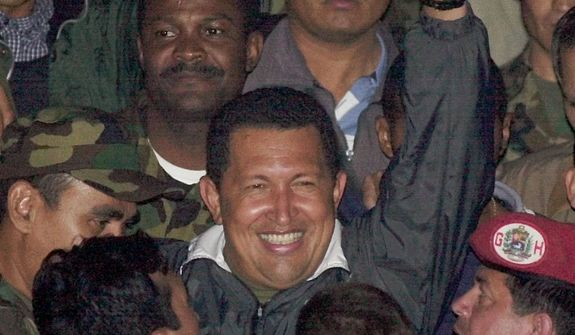 FILE - In this April 14, 2002 file photo, Venezuela's President Hugo Chavez gestures to supporters as he arrives to Miraflores presidential palace after being freed by his military captors two days after the military announced he had resigned in Caracas, Venezuela. Venezuela's Vice President Nicolas Maduro announced on Tuesday, March 5, 2013 that Chavez has died at age 58 after a nearly two-year bout with cancer. During more than 14 years in office, Chavez routinely challenged the status quo at home and internationally. He polarized Venezuelans with his confrontational and domineering style, yet was also a masterful communicator and strategist who tapped into Venezuelan nationalism to win broad support, particularly among the poor. (AP Photo/Dario Lopez-Mills, File)