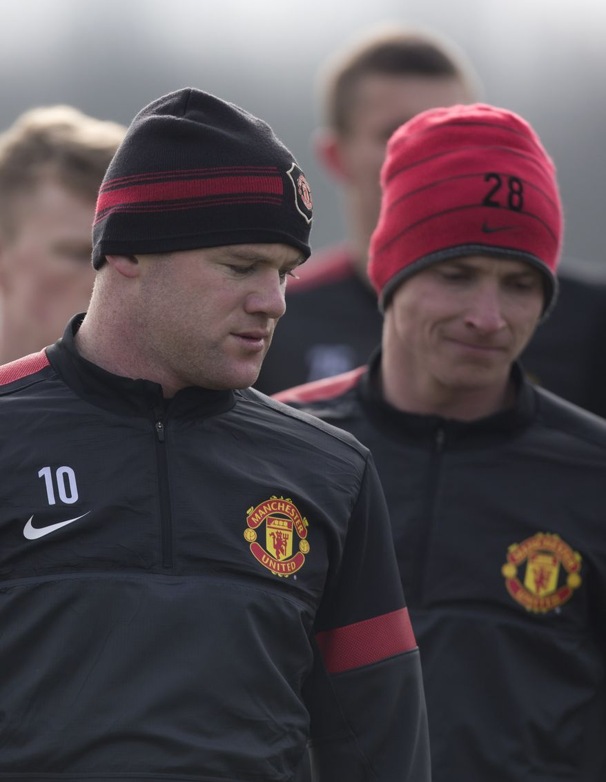 Manchester United's Wayne Rooney, left, trains with teammates at Carrington training ground in Manchester, Monday, March 4, 2013. Manchester United will play Real Madrid in a Champions League round of 16 soccer match on Tuesday. (AP Photo/Jon Super)