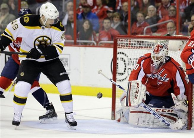 Boston Bruins center Rich Peverley (49) tries to get around to the puck deflected by Washington Capitals goalie Braden Holtby (70) in the second period of an NHL hockey game, Tuesday, March 5, 2013, in Washington. (AP Photo/Alex Brandon)