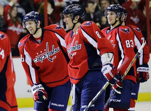 Washington Capitals right wing Eric Fehr (16) celebrates with left wing Alex Ovechkin (8), of Russia, forward Jay Beagle (83) and others after an NHL hockey game against the Boston Bruins, Tuesday, March 5, 2013, in Washington. Fehr scored the winning goal for their 4-3 overtime victory. (AP Photo/Alex Brandon)