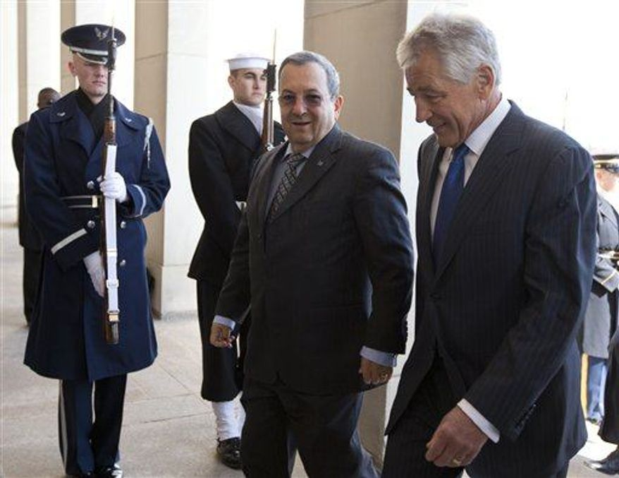 Defense Secretary Chuck Hagel, right, and Israeli Defense Minister Ehud Barak walk together into the Pentagon as Hagel hosts an honor cordon to welcome Barak to the Pentagon, Tuesday, March 5, 2013. (AP Photo/Carolyn Kaster)