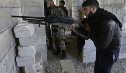 ** FILE ** Free Syrian Army fighters take their positions as they observe the Syrian army forces base of Wadi al-Deif at the front-line town of Maaret al-Numan in Syria's Idlib province on Tuesday, Feb. 26, 2013. (AP Photo/Hussein Malla)