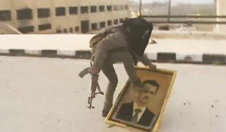 ** FILE ** In this Sunday, March 3, 2013, image taken from video obtained from the Shaam News Network, which has been authenticated based on its contents and other AP reporting, a Syrian rebel fighter stomps on a picture of Syrian President Bashar Assad within the police academy complex in Khan al-Asal, in the provence of Aleppo, Syria. (AP Photo/Shaam News Network via AP video)